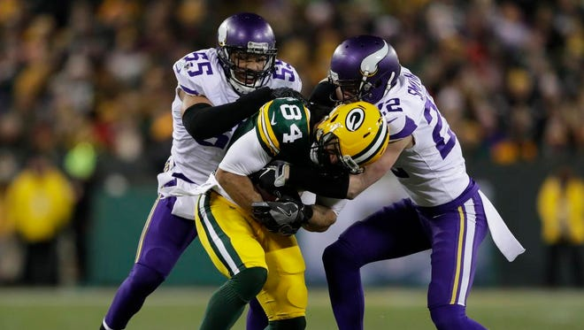 Green Bay Packers tight end Lance Kendricks (84) is brought down by Minnesota Vikings outside linebacker Anthony Barr (55) and free safety Harrison Smith (22) in the second quarter Saturday, December 23, 2017, at Lambeau Field in Green Bay, Wis.