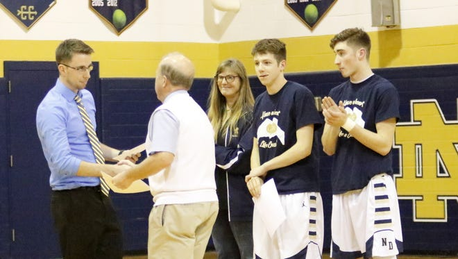 Notre Dame boys basketball coach Bill Hopkins presents Crusaders junior varsity coach Max Young a certificate of recognition for helping to save the life of Gary Raupers on Dec. 12 before a game at Notre Dame. Also pictured, from left, are Wendi Raupers, Cullen McWhorter and Gary Raupers II. McWhorter was also honored for helping to save the life of the older Raupers.