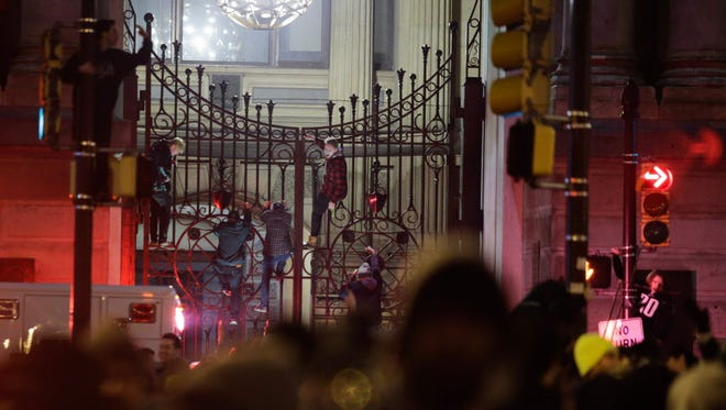 Fans climb City Hall fence while celebrating in Center City after the Philadelphia Eagles defeated the New England Patriots in Super Bowl LII.