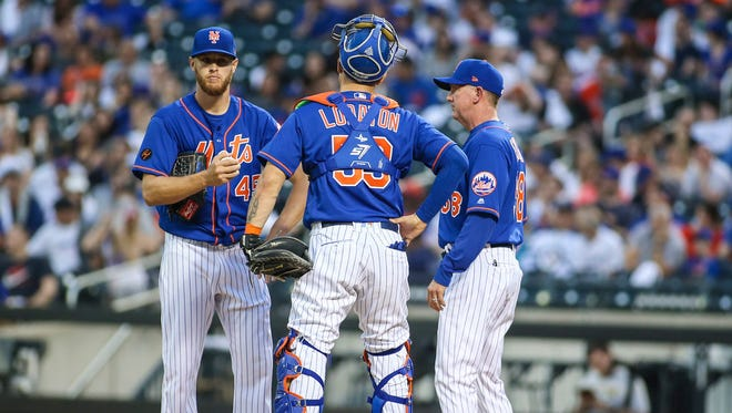 New York Mets pitching coach Dave Eiland (58) has a meeting with pitcher Zack Wheeler (45) and catcher Jose Lobaton (59) in the first inning against the Colorado Rockies at Citi Field.