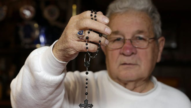 In this 2014 photo, Korean War veteran Ronald Ziolecki holds a rosary exactly like the one found in the belongings of a close friend who was killed in Korea. Ziolecki, of West Allis, dropped out of high school in 1949 to join the Marines. On June 6, he'll receive his high school diploma.