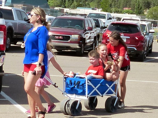 A couple of children hitch a ride to the games.