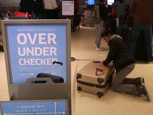A passenger repacks luggage before it is screened by a new explosives detection system on May 1 at Newark Liberty International Airport in New York City. The Transportation Security Administration is using the automated explosive screening system at the airport's Terminal C.