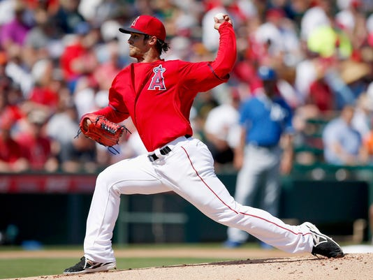 Los Angeles Angels' C.J. Wilson throws a pitch against the Kansas City Royals during the first inning of a spring training baseball game Friday, March 21, 2014, in Tempe, Ariz. (AP Photo/Ross D. Franklin)