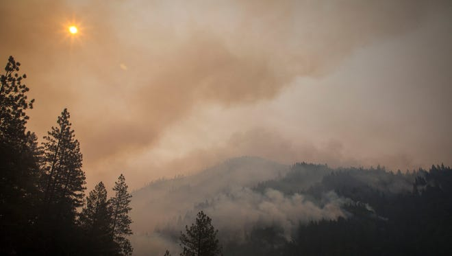 The sun peeks through the smoke and burned out trees near Whiskeytown Lake along Highway 299 on Monday July 31, 2018 near Redding.