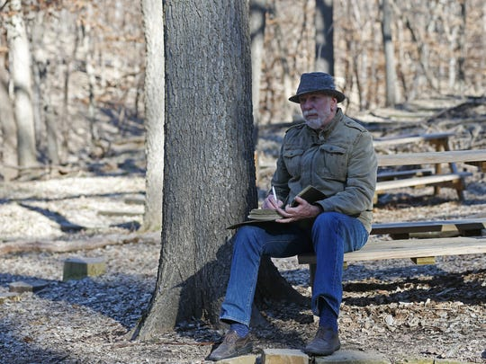 Bruce Hopkins, 75 of Sioux City, sits among the trees