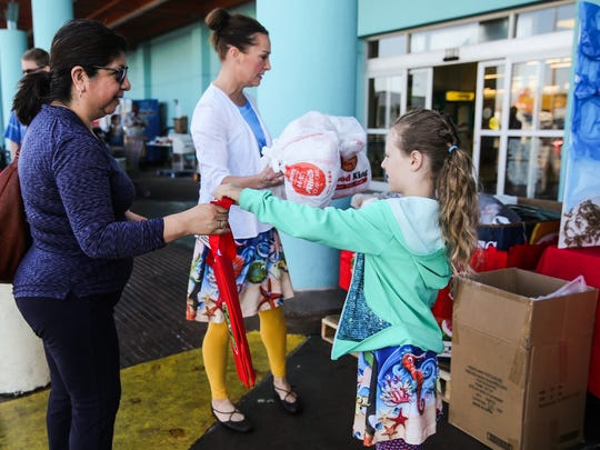 Ella Elkins, 8, gives Virginia Reyes a reusable grocery