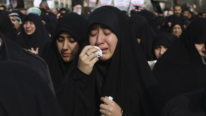 """A women weeps while mourning during a demonstration over the U.S. airstrike in Iraq that killed Iranian Revolutionary Guard Gen. Qassem Soleimani, in Tehran, Iran, Jan. 3, 2020. Iran has vowed """"harsh retaliation"""" for the U.S. airstrike near Baghdad's airport that killed Tehran's top general and the architect of its interventions across the Middle East, as tensions soared in the wake of the targeted killing. (AP Photo/Vahid Salemi)"""