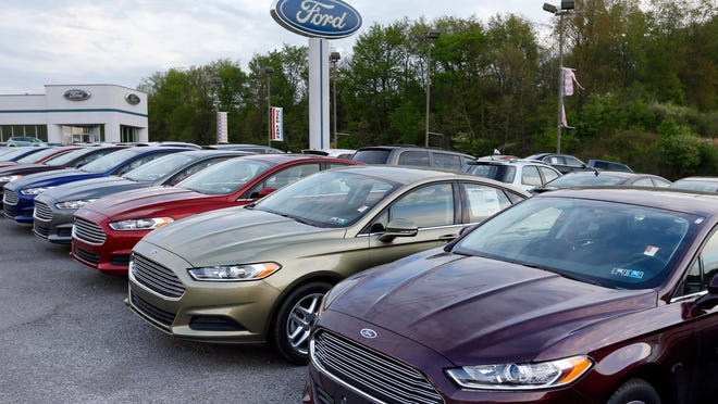 In this 2013 photo, new 2013 Ford Fusions are seen at an automobile dealer in Zelienople, Pa. U.S. auto sales slowed slightly in June 2014 but still maintained a healthy pace despite a record-setting string of safety recalls at General Motors and a slowdown in truck sales at Ford. Ford's U.S. sales chief John Felice said sales picked up at the end of June as automakers started promoting Independence Day sales.