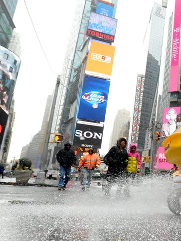 A worker spreads salt on the sidewalk in Times Square