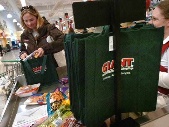 Laurie Meluzio packs her groceries in one of the three