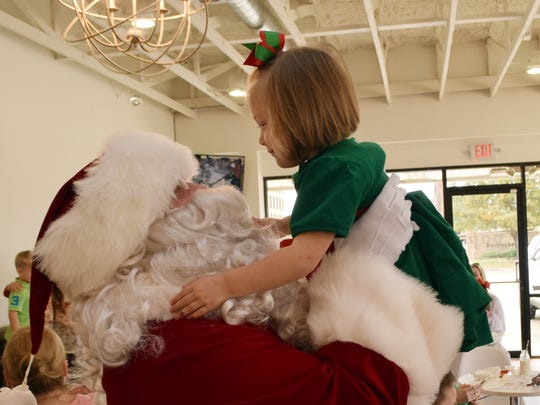 Santa Claus picks up Bayleigh Peterson, 2, at the annual Little Cakes with Big Attitude's Milk and Cookies with Santa held Saturday. Children were able to meet Santa Claus and Mrs. Claus, color, decorate cookies and have a picture session with Santa Claus.