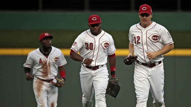 Cincinnati Reds second baseman Brandon Phillips (4), center fielder Jason Bourgeois (30) and right fielder Jay Bruce (32) run off the field after the top of the third inning of the MLB game between the Cincinnati Reds and the Los Angeles Dodgers at Great American Ball Park in Cincinnati on Wednesday, Aug. 26. After four innings the Reds trailed 6-0.