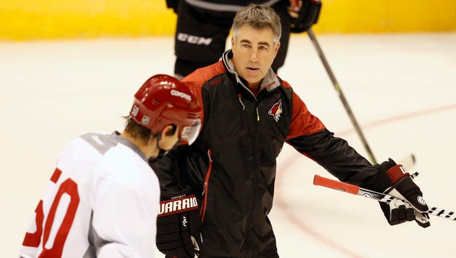 Phoenix Coyotes coach Dave Tippett instructs forward Antoine Vermette during training camp at Gila River Arena in Glendale on Saturday, September 19, 2015.
