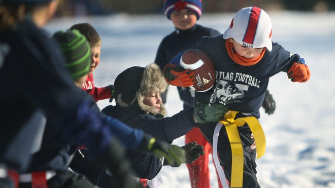 Left, Quinn Sadler,6, of Brighton reaches to tackle Joe DiMarco,5, also of Brighton during a flag football tournament at the Pavilion Lodge in Ellison Park in Irondequoit.