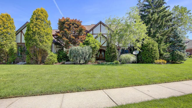 This five-bedroom, three-level Tudor-style home is all the more private  because of its lush landscaping. It's offered at $919,900.