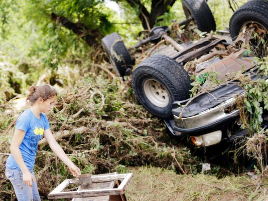 Jamie Myers looks for a neighbor's antiques that were washed into West Cache Creek bed after flooding in Cache, Okla., Sunday, May 24, 2015.