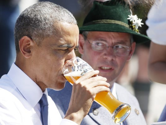 U.S. President Barack Obama drinks a beer during a visit to the village of Kruen, southern Germany, Sunday, June 7, 2015 prior to the G-7 summit in Schloss Elmau hotel near Garmisch-Partenkirchen where the summit will start later the day.