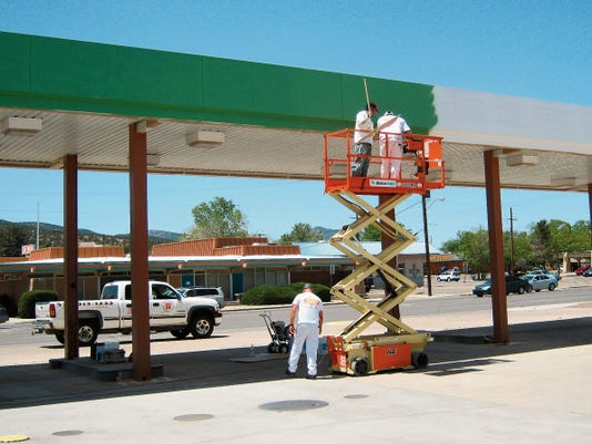 eyne Maynes of NM Professional Painters assisted on the ground as Rocky Maynes and Javier Alvarado painted the former filling station canopy at the Office of Sustainability in Silver City. Courtesy Photo