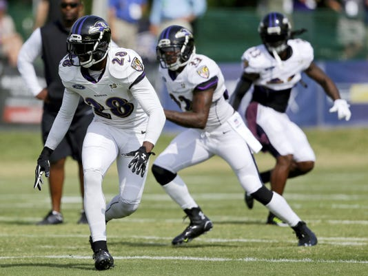 Baltimore Ravens defensive back Brynden Trawick, left, runs a drill during NFL football training camp Thursday in Owings Mills, Md.