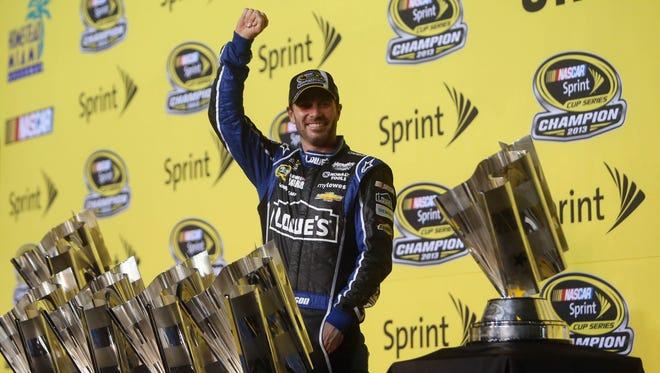 Jimmie Johnson poses for a photo with six Sprint Cup championship trophies after the 2013 season finale at Homestead-Miami Speedway.