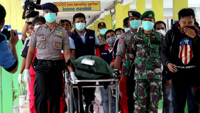 Military officers carry a plastic bag containing the body of a victim of AirAsia Flight 8501 at the main hospital in Pangkalan Bun, Indonesia, Friday, Jan. 2, 2015.