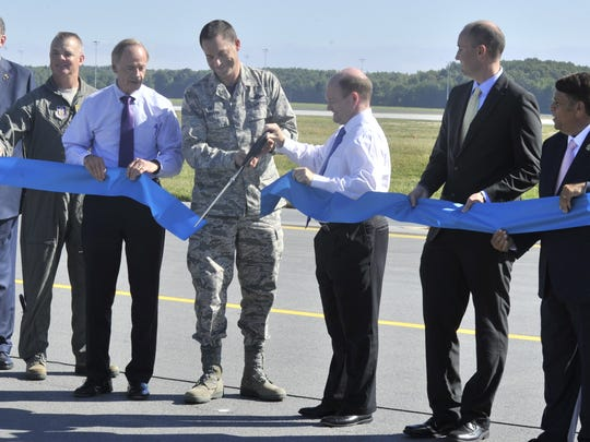 Dover Air Force Base commander Col. Ethan Griffin, flanked by Senators Tom Carper and Chris Coons, cuts a ceremonial ribbon marking the reopening of runway 01-19.