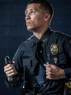 """Louisville Metro Police Sgt. Paul Humphrey poses for a portrait while holding one the several tourniquets he uses while on patrol.  """"It's an asset that I don't feel I'd be comfortable patrolling without it. Both for my personal safety and for the ability to help citizens who might find themselves injured,"""" Humphrey said."""