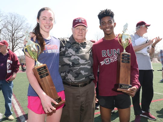 Sarah Flynn from The Ursuline School and Patrick Saint Ange from Ossining flank John Covert, after winning the Covert mile during the Ossining relays at the Anne M. Dorner Middle School in Ossining, April 14, 2018.