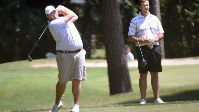 DSGA Amateur champion Jay Whitby (left) hits a tee shot as runner-up Jeff Whiteside looks on Wednesday at The Rookery North Golf Club in Milford.