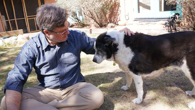 NMSU College of Education professor Chris Blazina pets his dog outside of his home. Blazina recently published two books related to his research on the emotional and psychological connection between men and dogs.