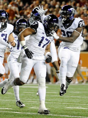 TCU safety Sam Carter (17) celebrates with teammates after intercepting a pass against Texas on Thursday at Darrell K Royal-Texas Memorial Stadium.