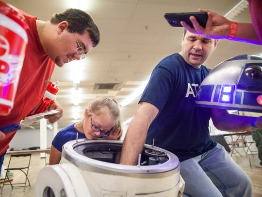 Andy Wiseman, right, explains the inner workings of the custom designed, remote-controlled R2D2 he helped build as Brooke Thomas, 9, center, and Damian Cave peek inside the creation during the Staunton Mall's Sci Fi Con on Sunday, April 12, 2015.