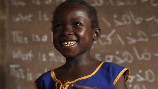 A young student, Lucy, smiles in front of a chalkboard at her school in Kenema District, in Sierra Leone's Eastern Province.