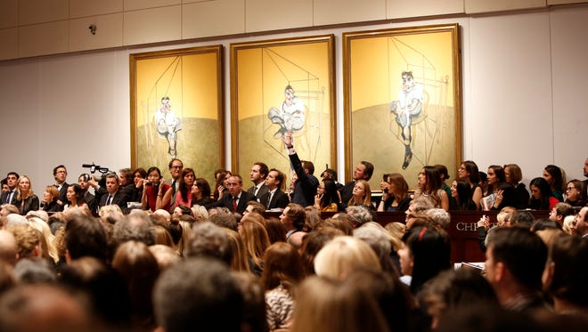 """Bidding ensues at Christie's New York for the 1969 painting by Francis Bacon, """"Three Studies of Lucian Freud"""" in New York on Nov. 12. 2013. It sold for over $142 million, a record for the most expensive artwork ever sold at auction."""
