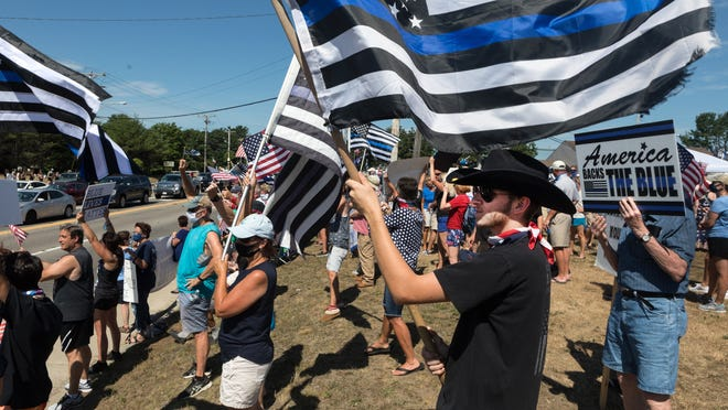 Philip Wainwright, from Kingston, holds a black and blue flag in support of police during a faceoff of protests between supporters of Back the Blue and Black Lives Matter on opposite sides of Route 139 near Marshfield High School and Roche Bros. on Sunday, July 26, 2020.