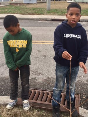 Zaieed Yawn (left) and C'andre Whiteside, both 10, tell the story of how a group of boys found a man's body inside a Cadillac at Lonsdale Homes on Sunday, Jan. 15, 2017.