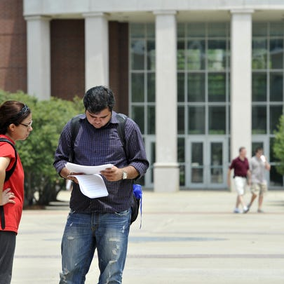 Students Silvia Guaz and Ashu Arora look over papers