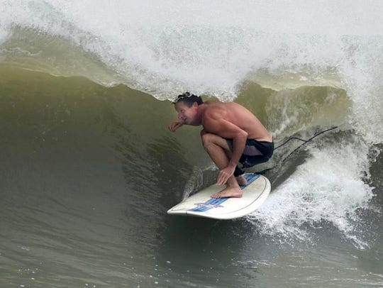 A surfer gets in the barrel of a wave caused by a swell