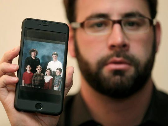 Jamey Anderson holds a photo on his phone of himself, bottom left, at the Word of Faith Christian School with classmates, from left, Liam, Risa Burgeson Pires, and Christopher Davies, and teachers Lisa Brown, top left, and Marty Roper, top right, during an interview in Charlotte, N.C. Throughout his adolescence, Anderson says he was singled out as a rebel and suffered some of the most brutal treatment in the church. Among his transgressions: making a funny face at a classmate.