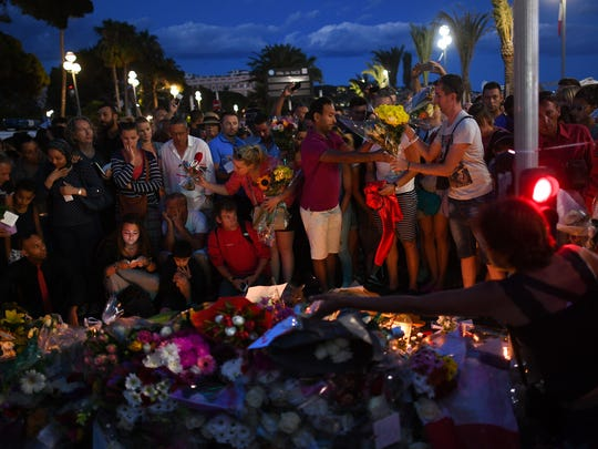 People visit the scene of a terror attack on the Promenade