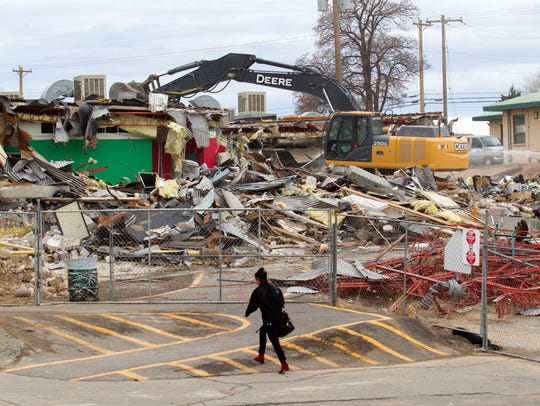 Demolition of the 400 building continues on Monday at Farmington High School.