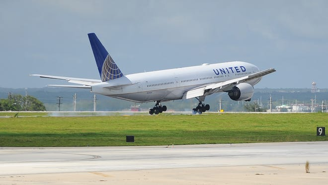 In this file photo, a United Airlines flight lands on a runway at the A.B. Won Pat International Airport. Falling oil prices could lead to a drop in airfares.