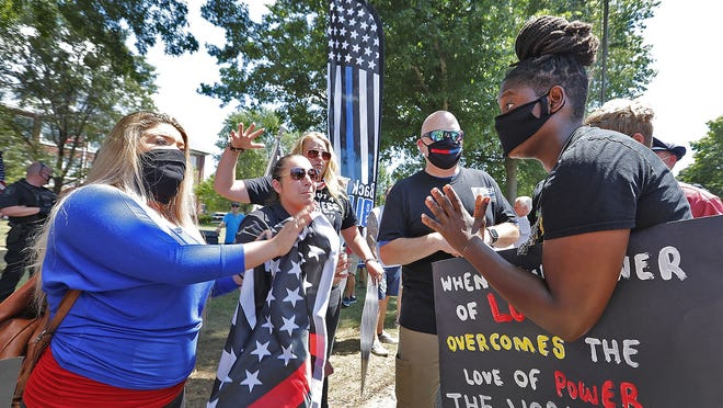 Anne Pungitore of Hingham, left talks with BLM protester  Tru Edwards at right who came from Boston to counter protest police supporters.   Supporters of local police line the street in from of the Hingham Police station on Tuesday July 28, 2020 Greg Derr/The Patriot Ledger