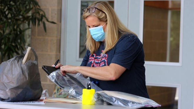 Shelby Middle School teacher Melissa Wilson prepares Chomebooks to be given to students.