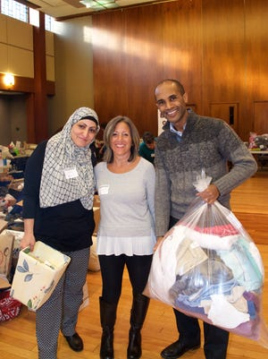 Obaida Omar, Lisa Hoyt and Getachew Beshir at the event, which continued a long tradition of helping refugees.