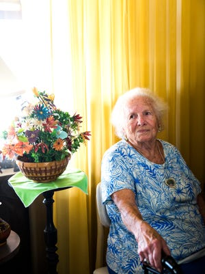 """Hedwig """"Hedy"""" Gillhuber sits next to one of her homemade flower bouquets, made from fish bones, on Wednesday, January 10, 2018, in Naples. Gillhuber and her husband built the Aqualane Shores home in the 1950s. At 104, she now lives alone."""