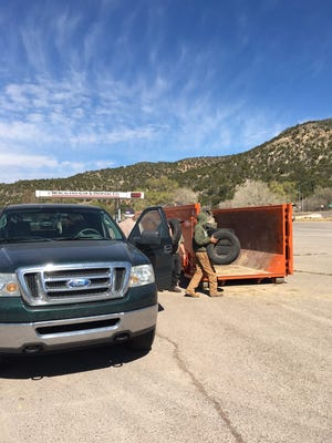 AmeriCorps volunteers unload scrap tires at Mescalero Tribal Store parking lot.