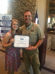 Home Builders Assn. President Kevin Bond presents a $1,000 scholarship check to Paige Decker at the group's June luncheon.