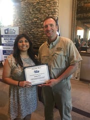 Home Builders Assn. President Kevin Bond presents a $1,000 scholarship check to Amanda Meza during the group's June luncheon.